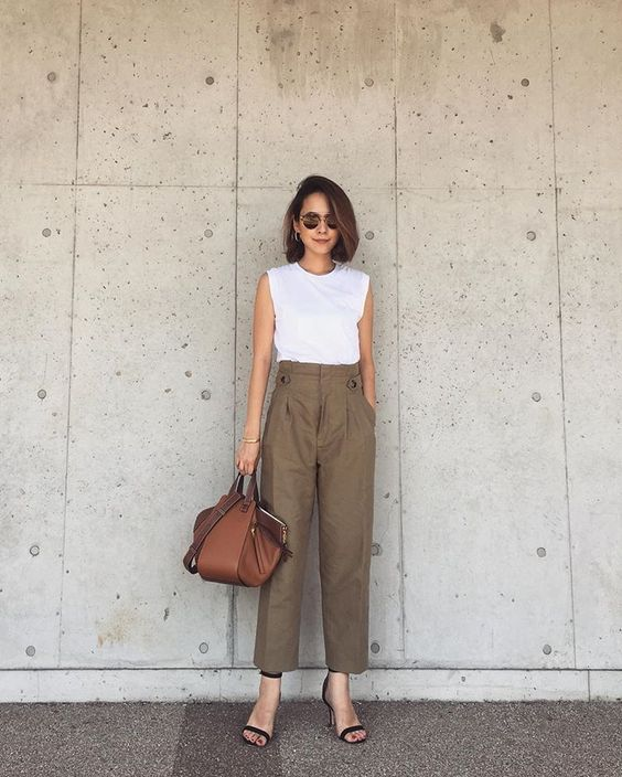 a white sleeveless top, olive green pants, black heels and a brown top handle bag of a quirky shape