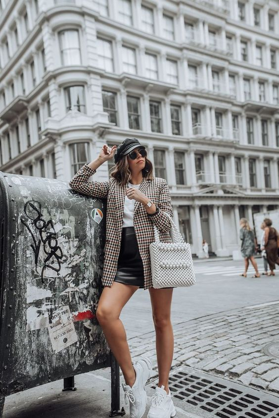 a white tee, a black leather mini, a plaid oversized blazer, white trainers and a pearl bag