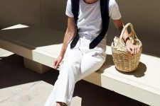 a white tee and jeans, black bow mules, a black sweater on the shoulders and a basket bag