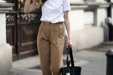 a white tee, brown high waisted pants, black lace up sandals and a larrge bucket bag for work
