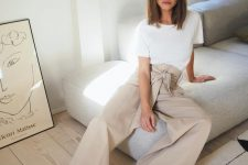 a white tee, tan high waisted wideleg pants, white strappy sandals for a minimal look