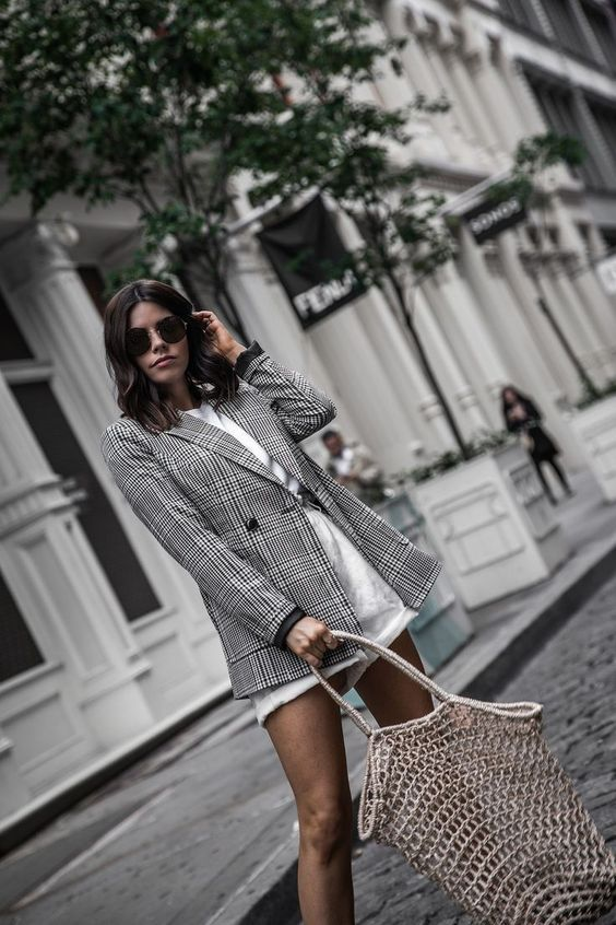 a white tee, white denim shorts, a grey plaid oversized blazer and a woven bag