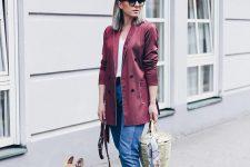 a white top, blue jeans, a burgundy pyjama-style blazer, blue flat mules and a basket bag
