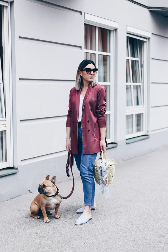 a white top, blue jeans, a burgundy pyjama-style blazer, blue flat mules and a basket bag
