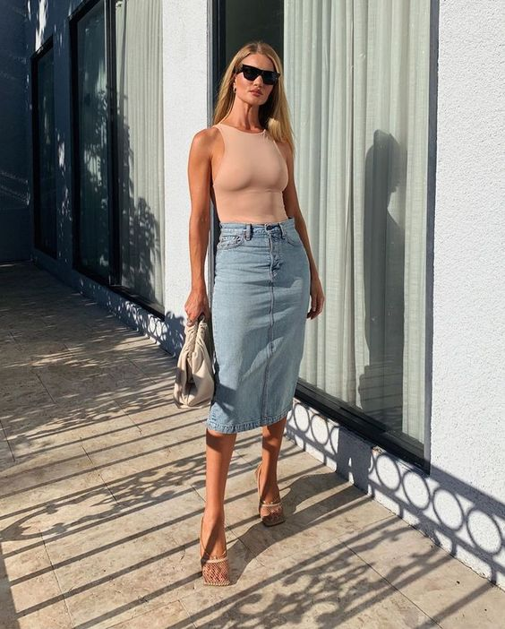 an edgy look with a blush halter top, denim midi, sheer net shoes and a white clutch