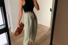 an edgy outfit with a black halter top, olive green baggy pants, black strappy sandals and a brown clutch
