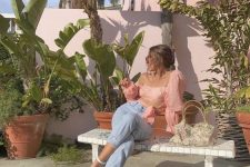 an edgy outfit with a pink crop top with puff sleeves, blue high waisted jeans and white shoes