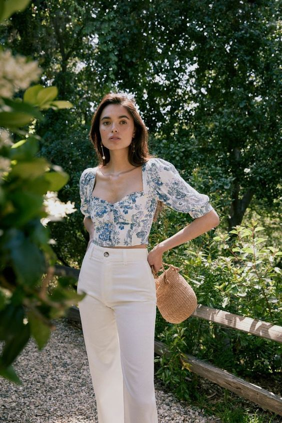 an elegant look with high waisted white jeans, a blue floral print crop top with puff sleeves and a basket