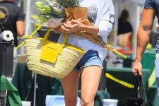an everyday look with a sweatshirt, denim shorts, white loafers and a bright yellow straw bag