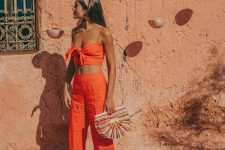 an orange suit with a tied crop top and linen pants, slippers and a colorful wooden bag