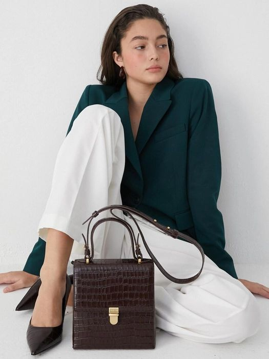 an oversized hunter green blazer, white pants, black shoes and a chocolate brown snakeskin top handle bag