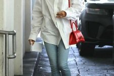 an oversized white shirt, blue jeans, whimsy heels and a small and chic red top handle bag