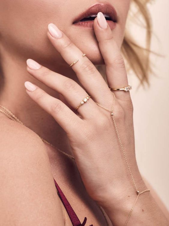 boho hand accessorizing with gold rhinestone midi and usual rings and a hand chain for an accent