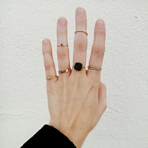 delicate gold rings stacked, a statement ring with a black rhinestone and gold midi rings that match