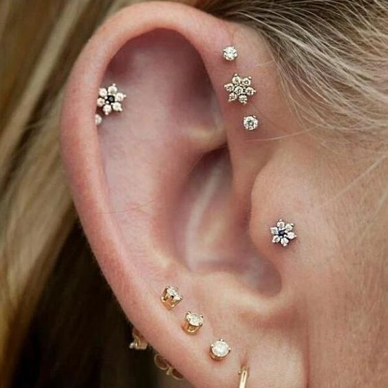 delicate stacked piercings on the lobe, helix and tragus, with mix and match pearl studs and floral ones