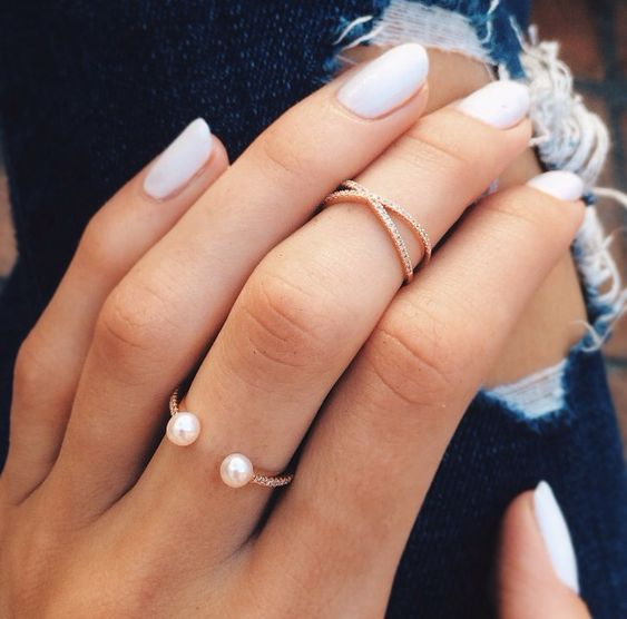 gorgeous stacked rings - a rhinestone and pearl one and a rhinestone midi ring look chic together