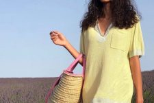 pink mini shorts and a yellow oversized and long shirt, a hot pink raffia bag