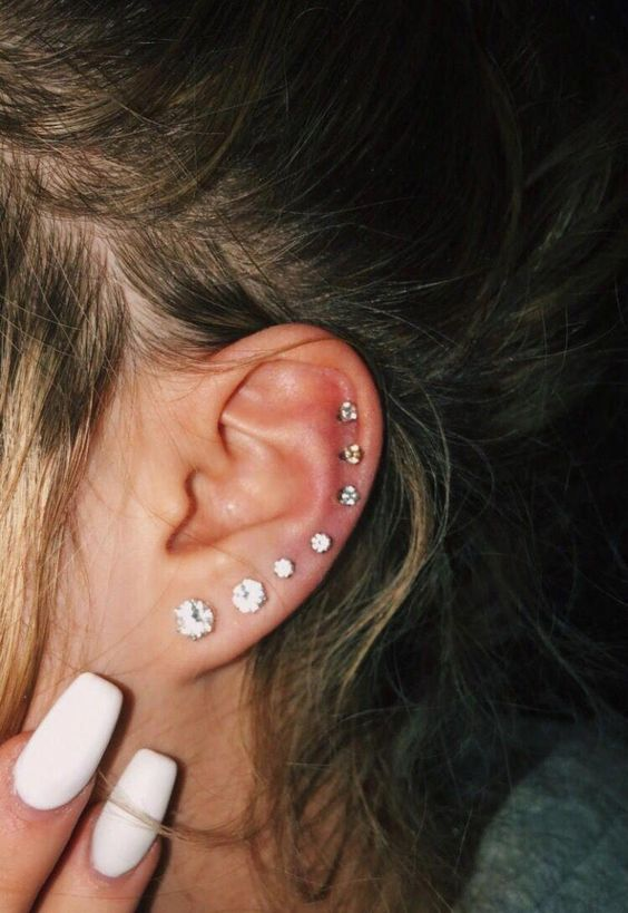 stacked ear piercings going up from the lobe to the upper part of the helix accessorized with matching shiny studs