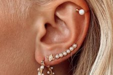 stacked lobe piercings with a chic set of pearl earrings and a matching ear cuff are very lovely