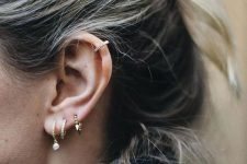 stacked lobe piercings with chic gold hoop earrings and a rhinestone hoop earring for accenting the helix piercing