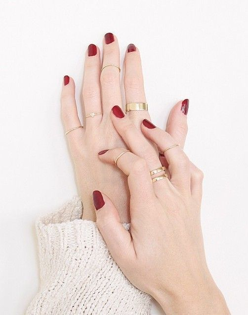 stylish modern gold rings and a delicate midi ring plus a red manicure for a bold look