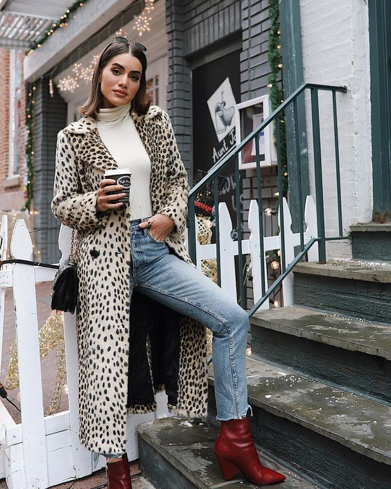 a bold look with a white turtleneck, blue jeans, red booties, an animal print coat and a black bag
