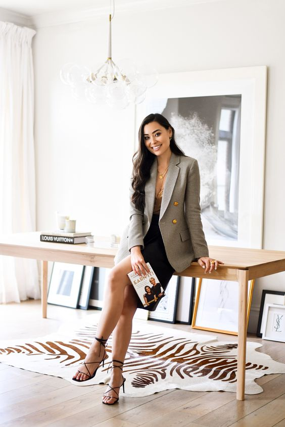 a chic look with a neutral top, a black skirt, a grey fitting plaid blazer and strappy shoes