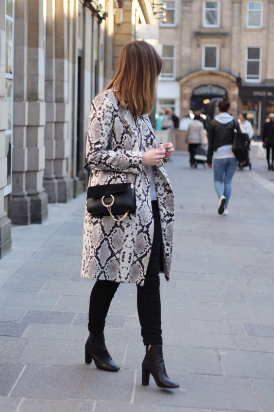a neutral top, black skinnies, black booties, a snake print trench and a black crossbody bag