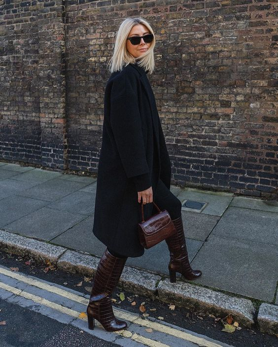 a total black look with a sweater, jeans, coat, burgundy reptile print boots and a bag