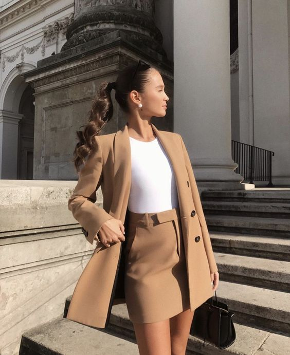 a minimalist fall work outfit with a white bodysuit, a camel fitting blazer and a mini skirt plus a black bag