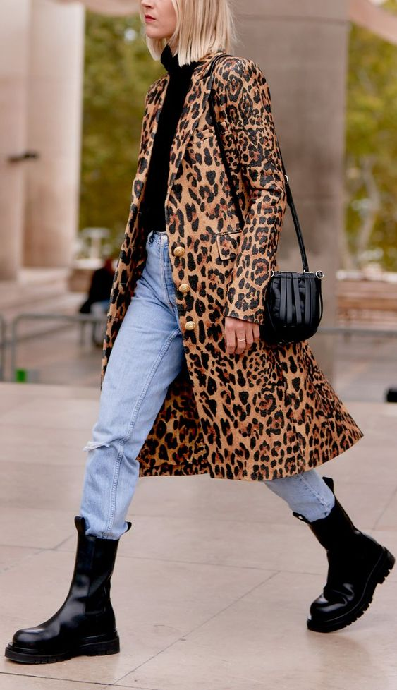 a trendy look with a black turtleneck, blue jeans, black combat boots and a leopard print coat