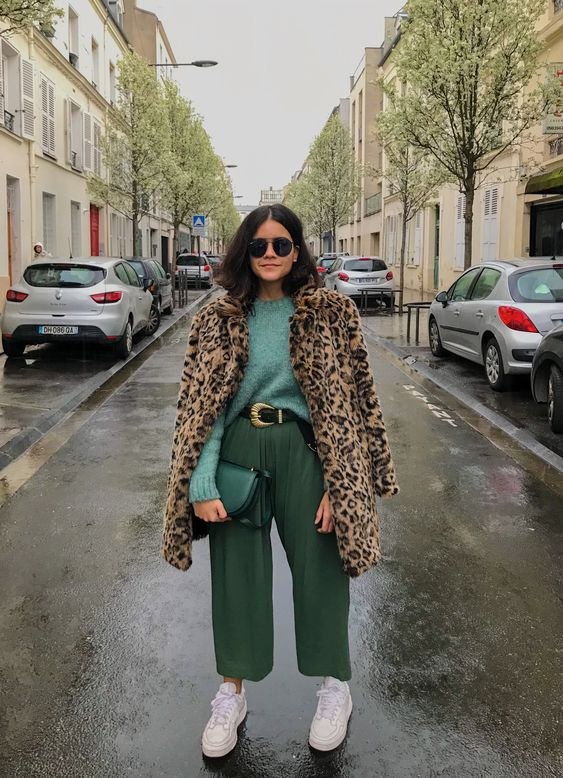 a stylish outfit with a green sweater, green pants, white trainers and a leopard print coat