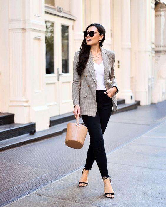 a white top, black raw hem skinnies, a grey plaid fitting blazer, black heels and a tan bucket bag
