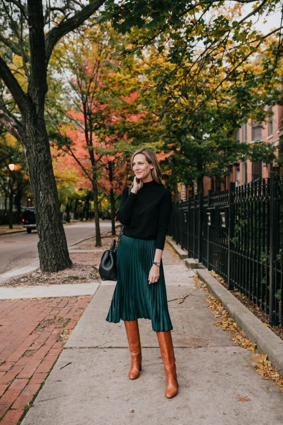 a black turtleneck, a hunter green plaid midi skirt, cognac slouchy boots and a black bag