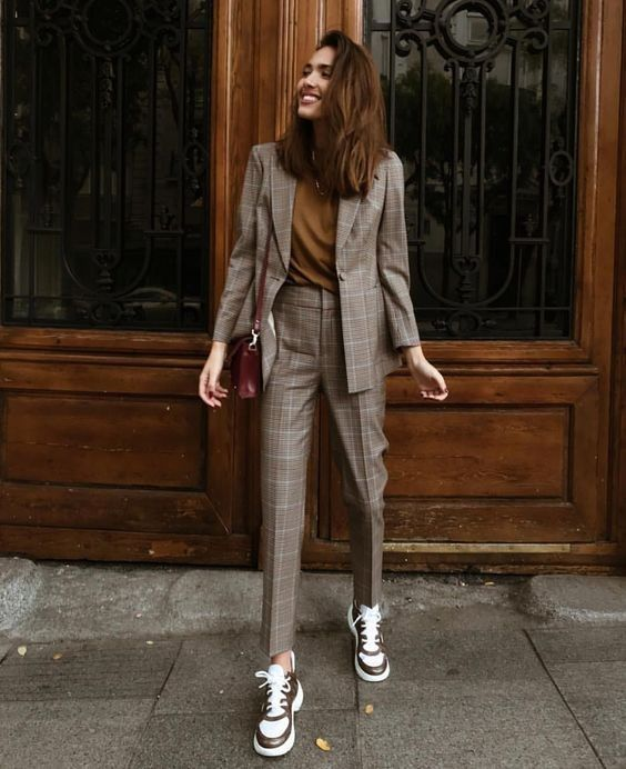 a grey plaid pantsuit with a mustard tee, a fitting blazer and trainers in two tones