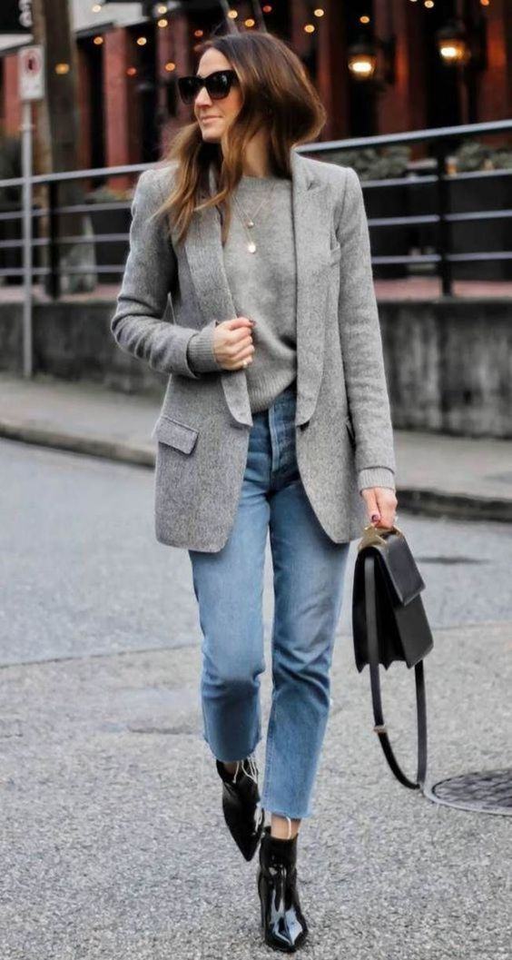 a grey cashmere top, blue jeans, black lacquer booties, a grey semi-fitting blazer and a black bag