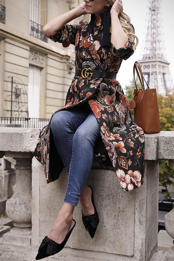 a chic outfit with a floral moody coat, blue skinnies, black bow mules and a logo belt