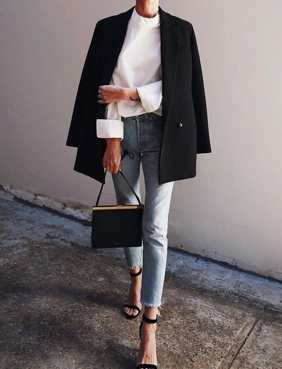 a cool work look with a white shirt, an oversized black blazer, blue high waisted jeans, black heels and a black bag