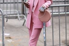 13 a girlish work outfit with a pink thin striped pantsuit, a light pink tee, light pink sneakers and a dusty pink bag