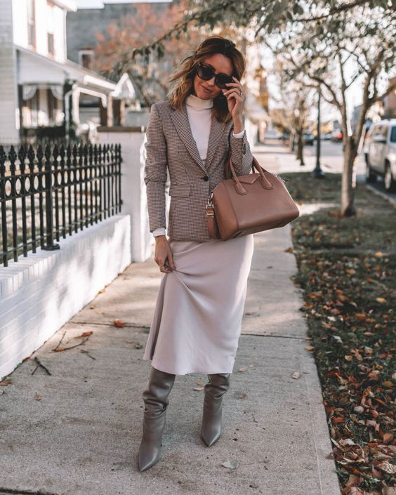 a stylish fall outfit with a white turtleneck, a slip skirt, a plaid blazer, grey slouchy boots and a camel bag