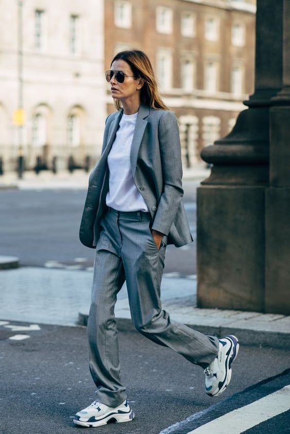 a comfortable grey pantsuit with an oversized blazer, a white tee and cool trainers for a casual work look