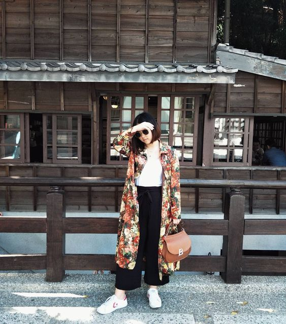 a white tee, black pants, white sneakers, a rust-colored bag and a floral trench for a touch of print and color