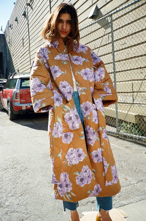 a white tee, blue jeans, mustard shoes and a rust-colored floral coat for a bright look