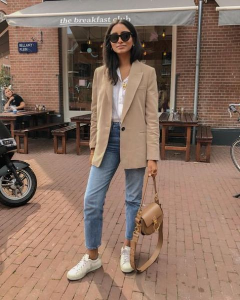 a white shirt, a tan oversized blazer, blue cropped jeans, white sneakers and a tan bag