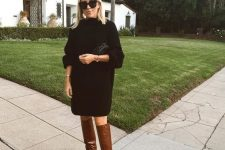 16 an oversized black sweater dress, brown reptile print slouchy boots, a black bag for the fall or winter