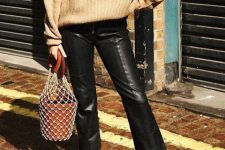 With beige oversized sweater, fishnet bag and black suede ankle boots