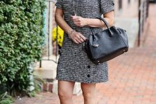 With black leather bag and black mules
