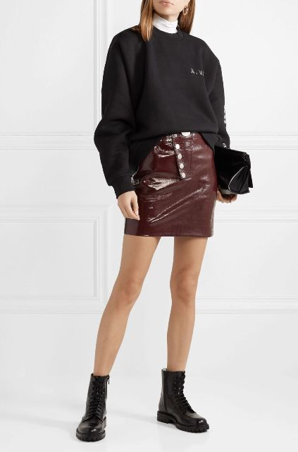 With black oversized sweatshirt, black clutch and black flat boots