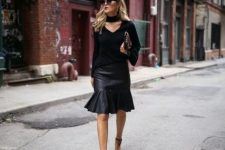 With black shirt, clutch and high heels