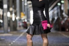 With black shirt, hot pink clutch and beige high boots